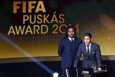 Colombiano James Rodríguez, do Real Madrid, recebe prêmio da Fifa do ex-jogador francês Christian Karembeu (E) em cerimônia em Zurique. 12/1/2015  REUTERS/Arnd Wiegmann