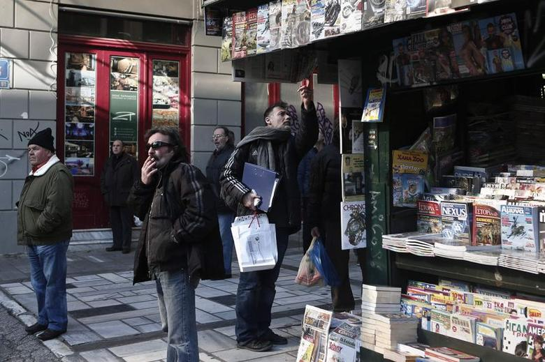 A man looks at newspapers at a kiosk as others look on in central Athens January 9, 2015. REUTERS/Alkis Konstantinidis (GREECE - Tags: SOCIETY)