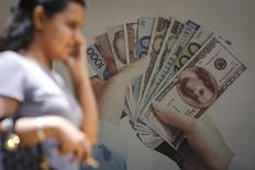 Consumidora passa em frente a uma propaganda de câmbio num banco em Mumbai, na Índia, em agosto de 2013. 19/08/2013 REUTERS/Danish Siddiqui