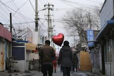 A woman holding a heart-shaped balloon walks with her partner at a residential area for migrant workers on Valentine's Day in Beijing February 14, 2013. REUTERS/Jason Lee
