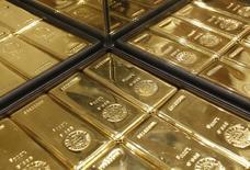 Слитки золото в магазине  Ginza Tanaka в Токио 18 апреля 2013 года. Цены на золото держатся чуть ниже 12-недельного максимума, так как ослабление доллара повышает спрос на низкорискованные активы. REUTERS/Yuya Shino