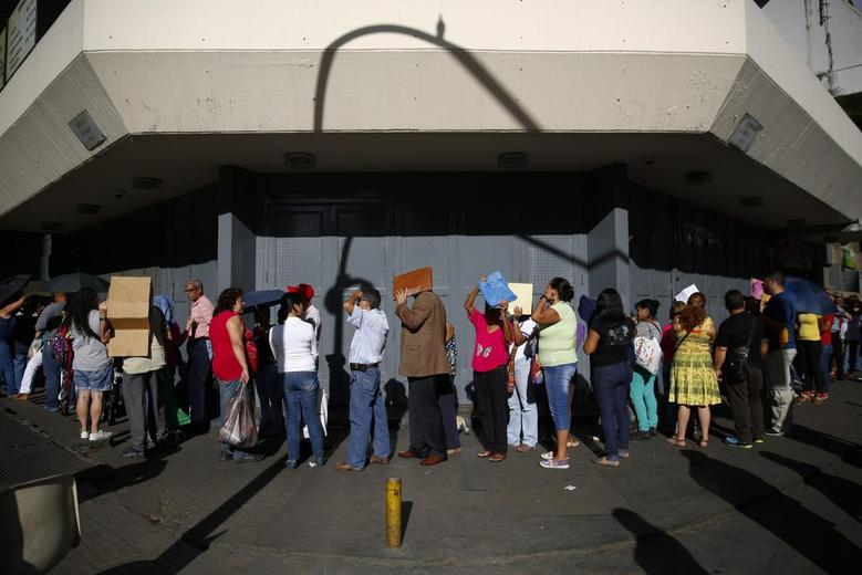 People line up outside a supermarket to buy toilet paper in Caracas January 12, 2015.  REUTERS/Jorge Silva