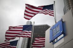 Флаги США у штаб-квартиры General Motors в Детройте. 28 мая 2009 года. Американский автоконцерн General Motors Co рассчитывает на увеличение прибыли в наступившем году, в основном в результате подъема на двух крупнейших для нее рынках - Китая и США. REUTERS/Mark Blinch