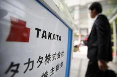 A man walks past a sign board of Japanese auto parts maker Takata Corp's Annual General Meeting in Tokyo June 26, 2014. REUTERS/Yuya Shino