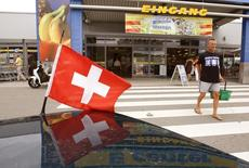 A file picture shows a car with a Swiss flag parked in front of a supermarket in the southern German town of Tiengen near the border with Switzerland July 15, 2010.  REUTERS/Arnd Wiegmann