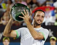 Viktor Troicki of Serbia holds the men's singles trophy after defeating Mikhail Kukushkin of Kazakhstan at the Sydney International tennis tournament in Sydney, January 17, 2015.    REUTERS/Jason Reed