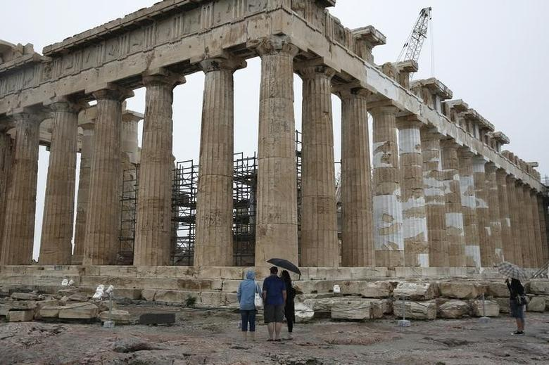 Tourists look at the temple of the Parthenon on the Acropolis hill on the eve of World Tourism Day (WTD) in Athens September 26, 2014. REUTERS/Yorgos Karahalis