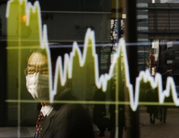 A man is reflected on an electronic board showing Japan's Nikkei average, outside a brokerage in Tokyo January 16, 2015. REUTERS/Toru Hanai