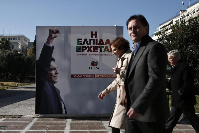 People walk past a banner with an image of opposition leader and head of radical leftist Syriza party Alexis Tsipras at the party's pre-election kiosk in Athens January 15, 2015.  REUTERS/Alkis Konstantinidis