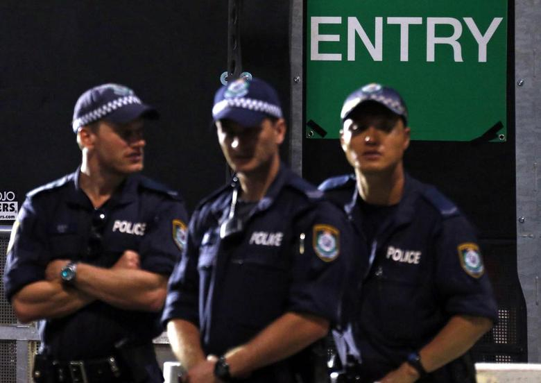 Police watch as people enter the harbour foreshore area in the city for the annual new year fireworks display on Sydney Harbour December 31, 2014. REUTERS/David Gray