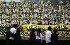 Students (in white) who survived the Sewol ferry disaster pay tribute to victims of the sunken passenger ship, after being discharged from a hospital at the official memorial altar in Ansan April 30, 2014. REUTERS/Kim Hong-Ji