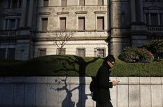 A man using his mobile phone walks past the Bank of Japan headquarters building in Tokyo December 19, 2014. REUTERS/Yuya Shino