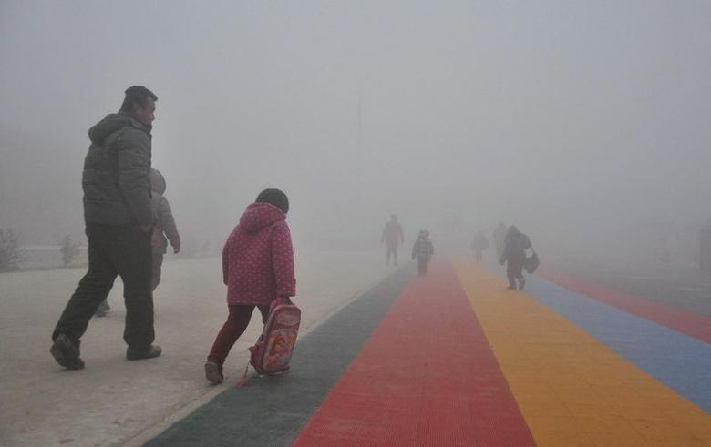 Parents walk primary school students to school amid thick haze in Chiping county, Shandong province January 16, 2015. REUTERS/China Daily