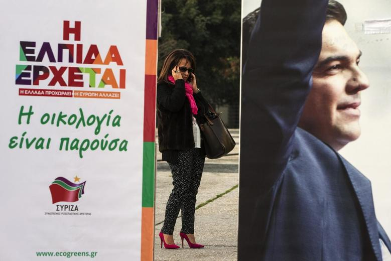 A woman talks on a mobile phone near a banner with an image of opposition leader and head of radical leftist Syriza party Alexis Tsipras at the party's pre-elections kiosk in Athens January 21, 2015. REUTERS/Marko Djurica