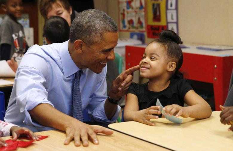 U.S. President Barack Obama touches the cheek of Akira Cooper during a visit to the Community Children's Center in Lawrence, Kansas January 22, 2015. REUTERS/Kevin Lamarque