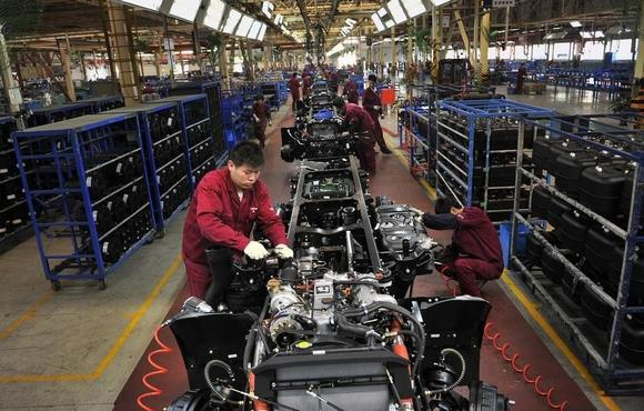 Workers install the chassis along a production line at a truck factory of Anhui Jianghuai Automobile Co. Ltd (JAC Motors) in Hefei, Anhui province May 5, 2014. REUTERS/Stringer