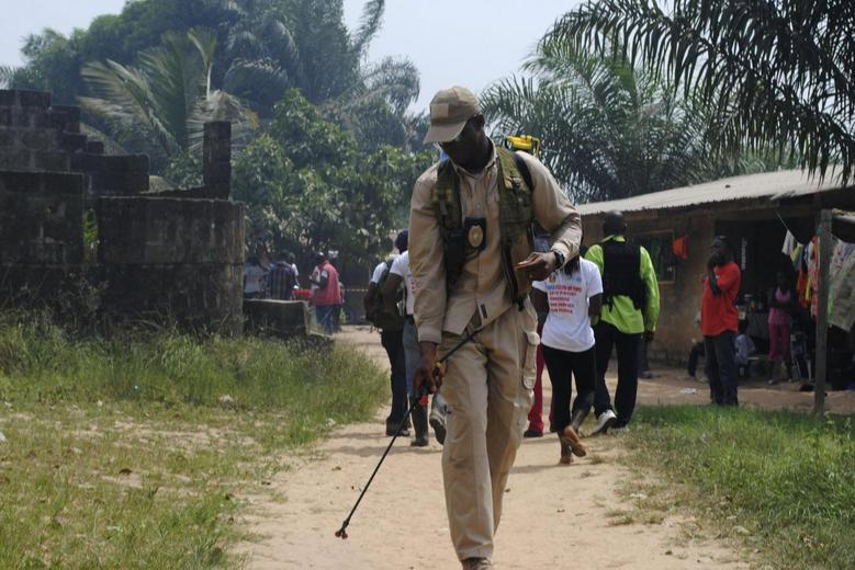 A health worker disinfects a road in the Paynesville neighborhood of Monrovia, Liberia, January 21, 2015. REUTERS/James Giahyue