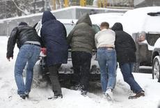 Люди толкают машину на заснеженной улице в Москве 25 декабря 2014 года. Выходные в Москве будут снежными, свидетельствует усреднённый прогноз, составленный на основании данных Гидрометцентра России, сайтов intellicast.com и gismeteo.ru. REUTERS/Sergei Karpukhin