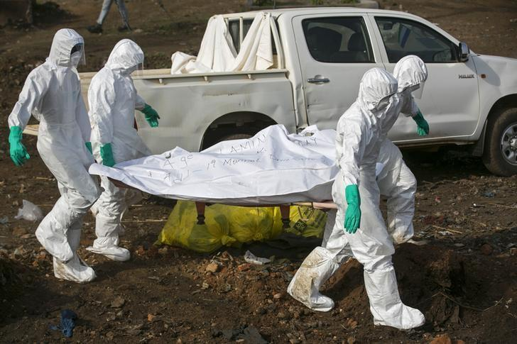 Health workers carry the body of a suspected Ebola victim for burial at a cemetery in Freetown December 21, 2014. REUTERS/Baz Ratner