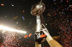 The Vince Lombardi Trophy is lifted into the air after the New Orleans Saints defeated the Indianapolis Colts in the NFL's Super Bowl XLIV football game in Miami, Florida, February 7, 2010.     REUTERS/Mike Segar