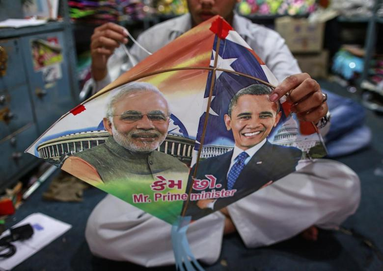 An employee ties threads on a kite, with portraits of Indian Prime Minister Narendra Modi (L) and U.S. President Barack Obama, ahead of Obama's visit, in Mumbai January 23, 2015. REUTERS/Danish Siddiqui