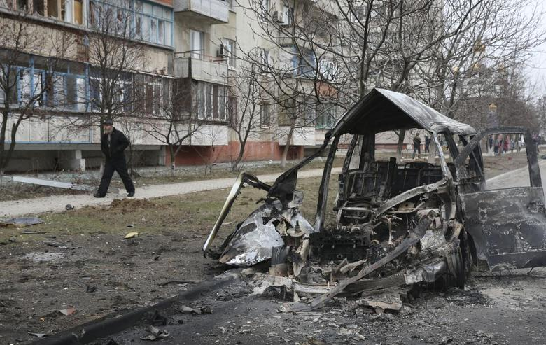 A man walks past a burnt-out vehicle after a shelling by pro-Russian rebels of a residential sector in Mariupol, eastern Ukraine, January 24, 2015.  REUTERS/Stringer