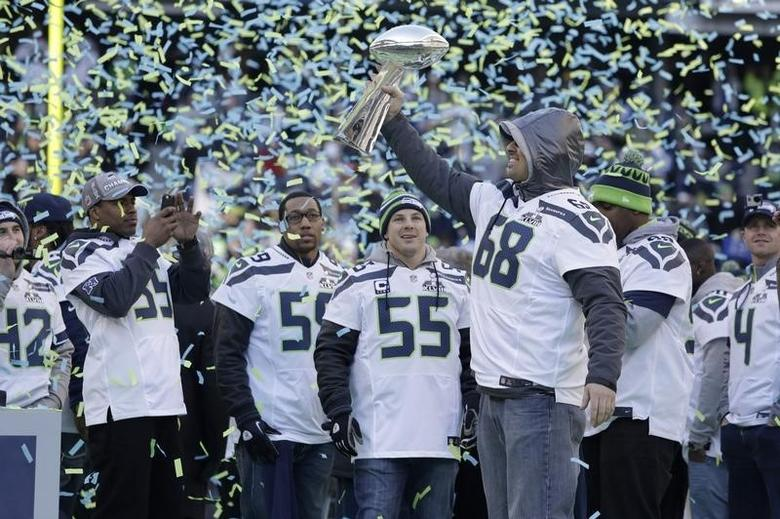 Seattle Seahawks' Breno Giacomini (68) holds the Vince Lombardi Trophy at Century Link Field after the NFL team's Super Bowl victory parade in Seattle, Washington February 5, 2014. REUTERS/Jason Redmond