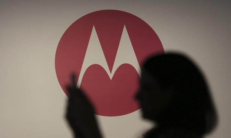 A woman takes a picture in front of a Motorola logo before the worldwide presentation of the Moto G mobile phone in Sao Paulo November 13, 2013.  REUTERS/Nacho Doce