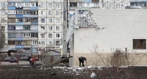 Люди убирают обломки у здания, пострадавшего в результате обстрела, в Мариуполе. 25 января 2015 года. Правительство Украины ввело режим чрезвычайной ситуации на востоке Украины, где с апреля продолжается вооруженный конфликт с сепаратистами, унесший более 5.000 жизней, включая 30 погибших в субботу от обстрела Мариуполя. REUTERS/Nikolai Ryabchenko