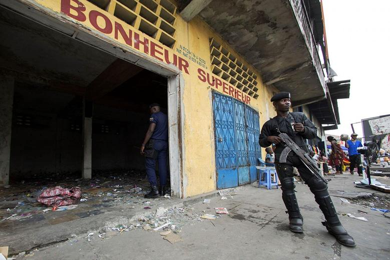 A police officer stands guard in front of a store that was looted during violent protests in Kinshasa, Democratic Republic of Congo January 23, 2015. REUTERS/Rey Byhre
