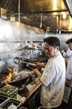 Vietnamese-American chef Charles Phan cooks inside the kitchen of his restaurant The Slanted Door in San Francisco in 2014, in this handout provided by Ed Anderson.     REUTERS/Ed Anderson/Reprinted with permission from photographer and Ten Speed Press, a division of Penguin Random House/Handout via Reuters