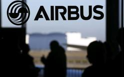 People are silhouetted past a logo of the Airbus Group during the Airbus annual news conference in Colomiers, near Toulouse January 13, 2015. REUTERS/Regis Duvignau