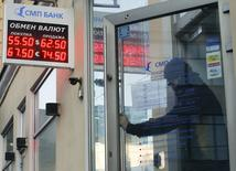 A man walks out of a bank office, with an electronic board show REUTERS/Maxim Zmeyev
