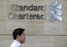An office worker walks past a Standard Chartered logo outside its head office in Singapore January 8, 2015. REUTERS/Edgar Su