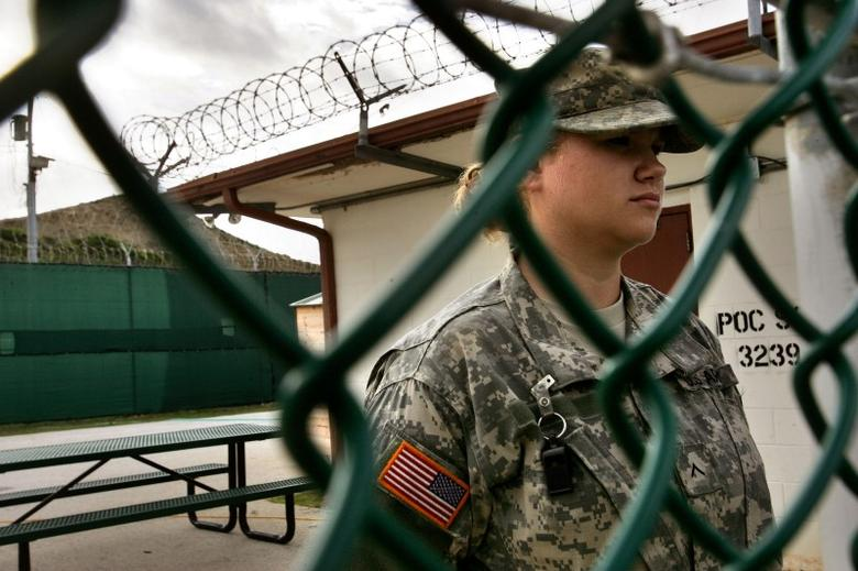 In this photo reviewed by U.S. military officials, a U.S. soldier guards a gate within the compound of the U.S. military-run prison in the Guantanamo Bay U.S. Naval Base, Cuba June 26, 2006. REUTERS/Brennan Linsley/Pool