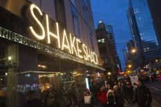 Passersby walk in front of the Shake Shack restaurant in the Manhattan borough of New York, December 29, 2014. REUTERS/Keith Bedford