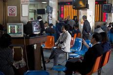 Розничные инвесторы в брокерской конторе Шанхае. 14 апреля 2014 года. Азиатские фондовые рынки, кроме Китая, выросли в январе благодаря стимулирующим мерам центробанков в нескольких регионах. REUTERS/Aly Song