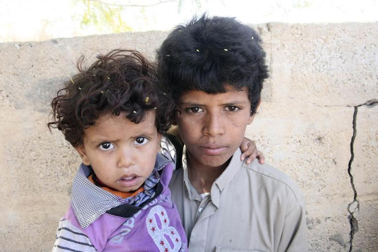 Mohammed Saleh Qayed Taeiman (R) poses for a photo with his younger brother outside their family's house in Marib province, Yemen, in this October 29, 2013 photo. REUTERS/Faroq al-Shaarani