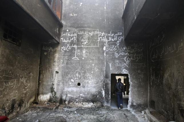 A man walks inside a damaged building with an Islamic flag drawn on the wall in the besieged town of Arbeen in the eastern Ghouta of Damascus January 17, 2015.  REUTERS/Yaseen Al-Bushy