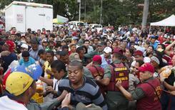 """Soldados venezolanos tratan de controlar a la multitud que se aglomeró para intentar comprar pollo en un Mega-Mercal, un mercado estatal subsidiado, en Caracas, 24 de enero de 2015.  Los dueños de una importante cadena de tiendas de Venezuela fueron detenidos por """"provocar"""" una """"guerra económica"""" en el país, anunció el domingo el presidente Nicolás Maduro sin mencionar el nombre del comercio que medios locales identificaron como las farmacias Farmatodo. REUTERS/Carlos Garcia Rawlins"""