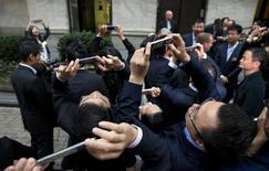 En la imagen, empleados y directivos de Alibaba Group Holding Ltd usan sus teléfonos móviles para tomar fotos en su salida a bolsa, en la Bolsa de Nueva York, el 19 de septiembre de 2014. China alcanzó los 649 millones de usuarios de internet a fines de 2014, de los que 557 millones usan móviles para conectarse, según un informe oficial publicado el martes, en una señal de que el mayor mercado mundial de teléfonos inteligentes continúa avanzando hacia el mundo móvil. REUTERS/Brendan McDermid