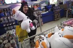 A girl poses with an Olaf plush toy from Disney's Frozen toy line at the Toys R Us store in Times Square in New York November 27, 2014.  REUTERS/Carlo Allegri