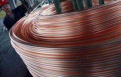 Un empleado desenrrolla alambre de cobre en Nantong, China, jun 18 2011. La industria del cobre en China está recortando la demanda de desechos del metal debido a los bajos márgenes por la debilidad de los precios, lo que podría desacelerar el crecimiento de la producción local de la materia prima refinada este año, dijeron fuentes de la industria. REUTERS/China Daily