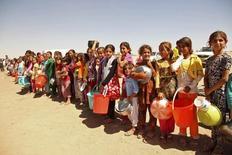 Várias pessoas da minoria yazidi, fugidas da violência na cidade iraquiana de Sinjar, fazem fila para receber alimentos num acampamento nos arredores da província de Dohuk, em setembro. 13/09/2014 REUTERS/Ari Jalal