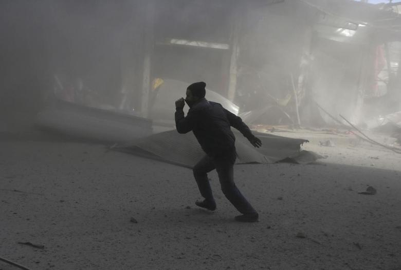 A man covers his nose as he runs after what activists said were at least 20 air strikes by forces loyal to Syria's President Bashar al-Assad in the Douma neighbourhood of Damascus February 5, 2015.  REUTERS/Bassam Khabieh