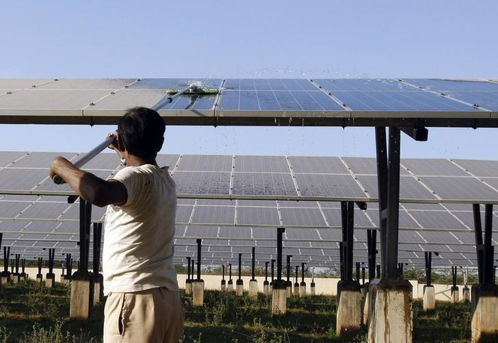 A worker cleans photovoltaic solar panels inside a solar power plant at Raisan village near Gandhinagar, in Gujarat, February 11, 2014. REUTERS/Amit Dave/Files