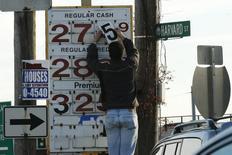 Una persona cambia los precios del combustible en una gasolinera en Medford, EEUU, dic 4 2014. La incertidumbre sobre el futuro de los precios del petróleo podría opacar las predicciones del Fondo Monetario Internacional para la economía global, dijo el viernes el equipo técnico de la entidad en una nota.   REUTERS/Brian Snyder