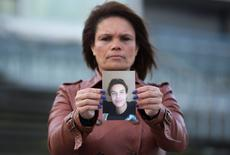 Ozana Rodrigues, the mother of Brian De Mulder, who left for Syria after being indoctrinated by Islamist group Sharia4Belgium, poses with a photo of her son outside the Antwerp courthouse, where the trial of the group is currently taking place, January 29, 2015. REUTERS/Yves Herman