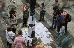 Pessoas olhando ofertas de trabalho coladas em poste no centro de São Paulo.  13/08/2014 REUTERS/Paulo Whitaker