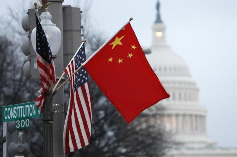 The People's Republic of China flag and the U.S. Stars and Stripes fly on a lamp post along Pennsylvania Avenue near the U.S. Capitol in Washington during Chinese President Hu Jintao's state visit, January 18, 2011. REUTERS/Hyungwon Kang